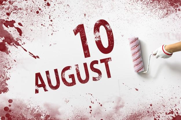 10 de agosto. día 10 del mes, fecha del calendario. la mano sostiene un rodillo con pintura roja y escribe una fecha del calendario sobre un fondo blanco. mes de verano, concepto de día del año.