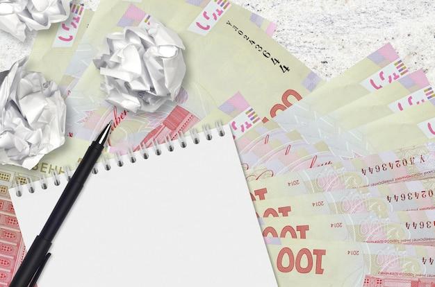 100 billetes de hryvnias ucranianas y bolas de papel arrugado con bloc de notas en blanco. malas ideas o menos concepto de inspiración. buscando ideas para inversión