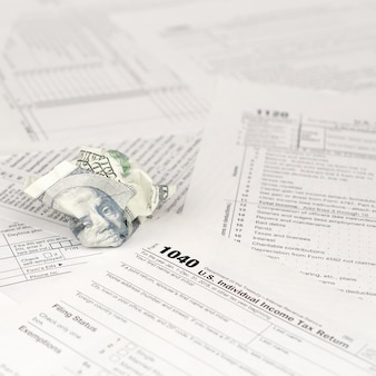 1040 formulario de declaración de impuestos sobre la renta individual y billete de cien dólares arrugado
