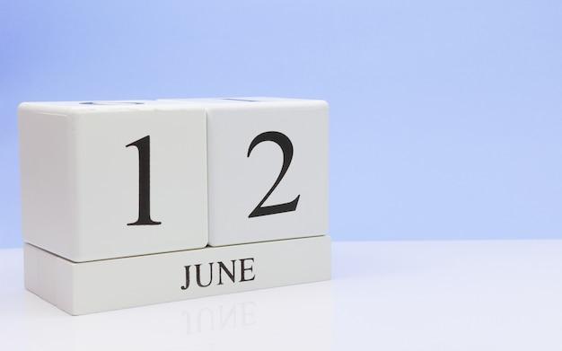 12 de junio. día 12 del mes, calendario diario sobre mesa blanca.