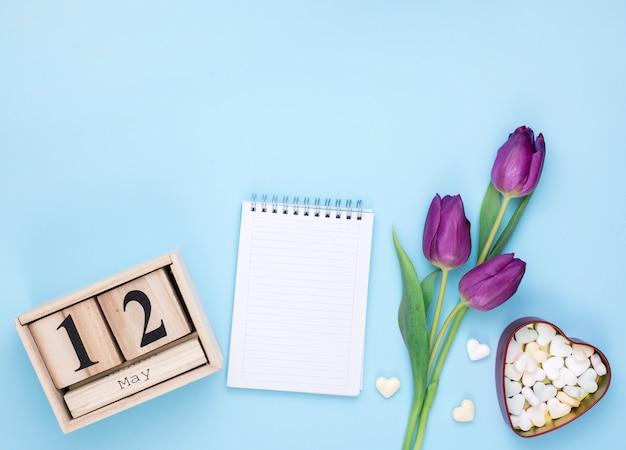 12 de mayo inscripción con bloc de notas y tulipanes.