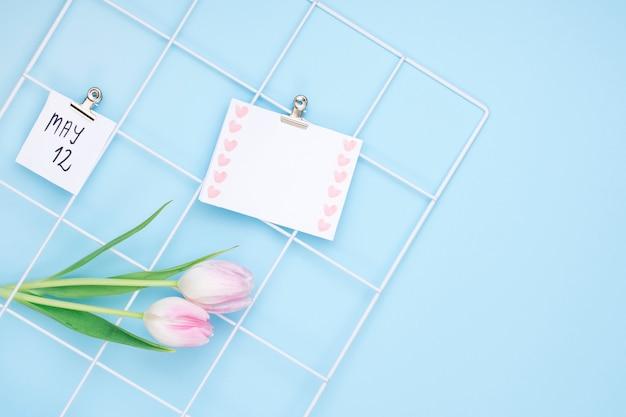 12 de mayo inscripción con papel en blanco y tulipanes.