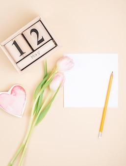 12 de mayo inscripción con tulipanes y papel en blanco.