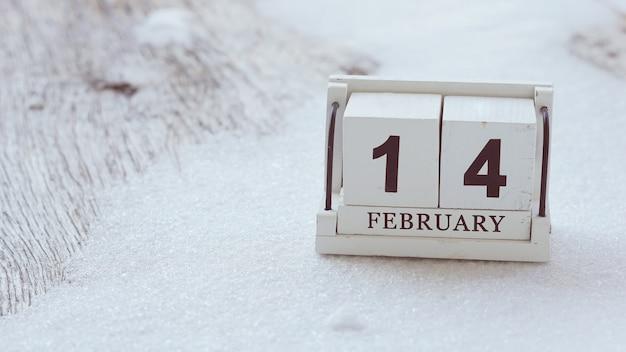 14 de febrero en el calendario de madera con nieve en la mesa de madera