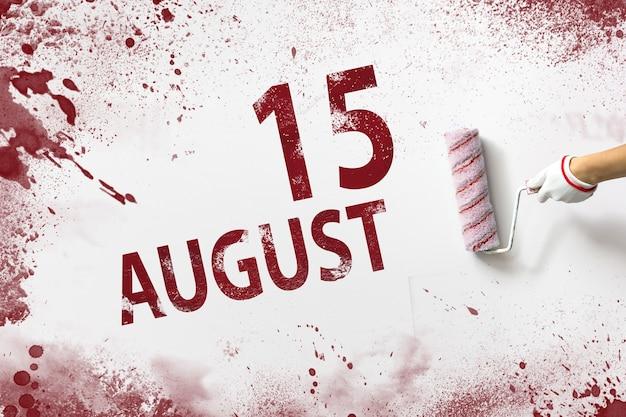 15 de agosto. día 15 del mes, fecha del calendario. la mano sostiene un rodillo con pintura roja y escribe una fecha del calendario sobre un fondo blanco. mes de verano, concepto de día del año.