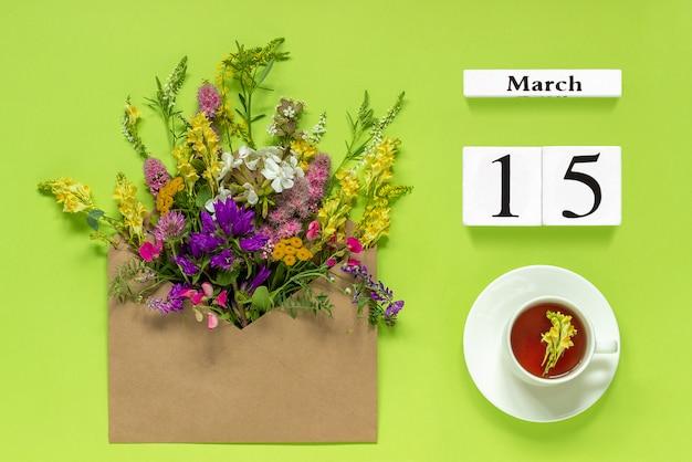 15 de marzo. taza de té, sobre kraft con flores multicolores en verde.