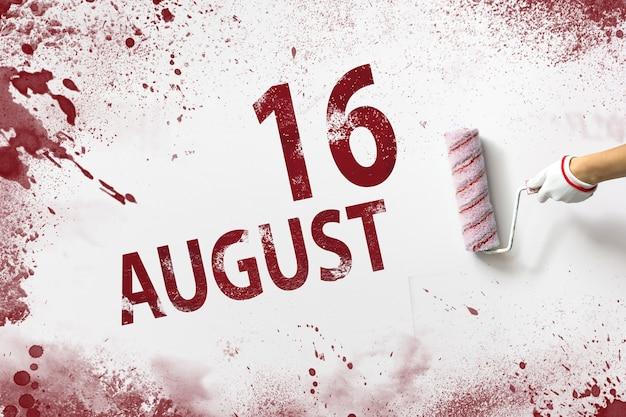 16 de agosto. día 16 del mes, fecha del calendario. la mano sostiene un rodillo con pintura roja y escribe una fecha del calendario sobre un fondo blanco. mes de verano, concepto de día del año.