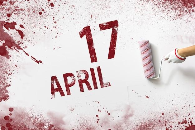 17 de abril. día 17 del mes, fecha del calendario. la mano sostiene un rodillo con pintura roja y escribe una fecha del calendario sobre un fondo blanco. mes de primavera, concepto de día del año.