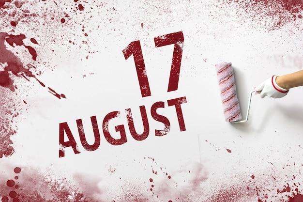 17 de agosto. día 17 del mes, fecha del calendario. la mano sostiene un rodillo con pintura roja y escribe una fecha del calendario sobre un fondo blanco. mes de verano, concepto de día del año.