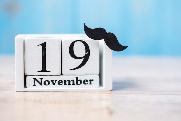 19 de noviembre calendario y bigote en mesa de madera. padre, día internacional del hombre, conciencia del cáncer de próstata