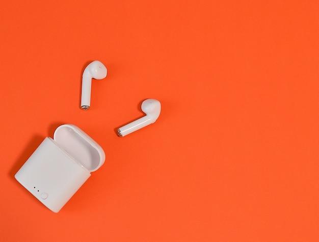 2 auriculares inalámbricos blancos en la oreja con bluetooth en una pared naranja. lay flat