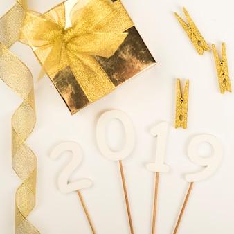 2019 cifras de año nuevo en palos entre decoraciones.