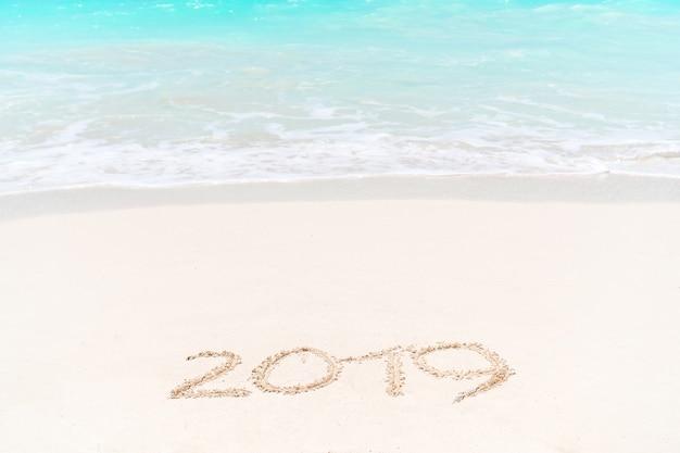 2019 escrito a mano en la playa de arena con suave ola oceánica en el fondo
