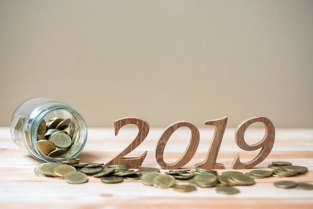 2019 feliz año nuevo con pila de monedas de oro y número de madera en mesa