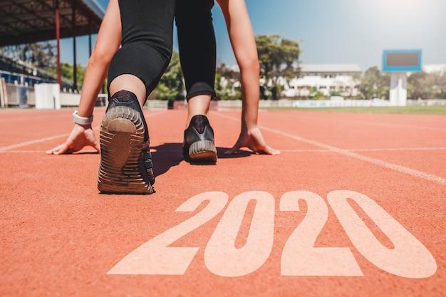 2020 año nuevo, atleta mujer que comienza en línea para comenzar a correr con el número 2020 comienzo para año nuevo.
