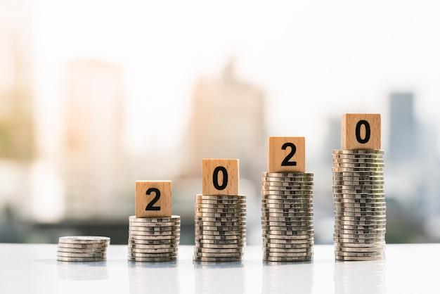 2020 bloques de madera en la parte superior de la pila de monedas en fondos de la ciudad.