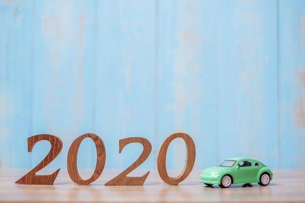 2020 feliz año nuevo con coche en mesa de madera con espacio de copia