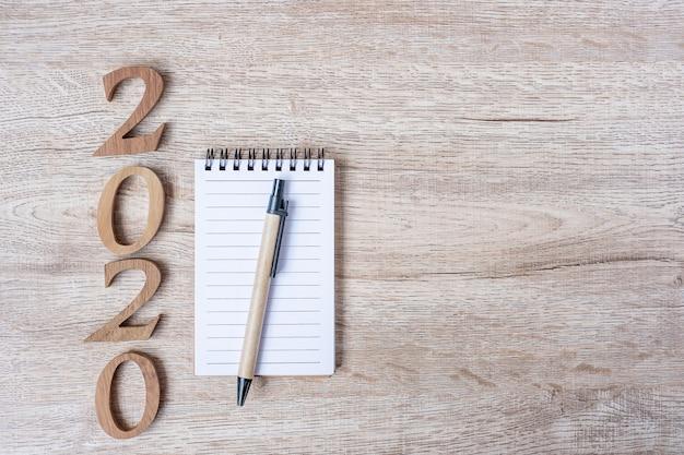 2020 feliz año nuevo con cuaderno de papel, bolígrafo y número de madera