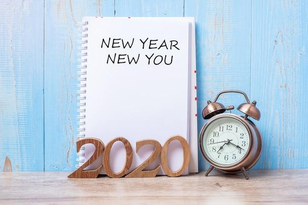 2020 feliz año nuevo nuevo con cuaderno, reloj despertador retro y número de madera en la mesa