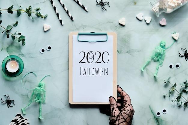 2020 texto de halloween en la libreta del portapapeles en la mano.