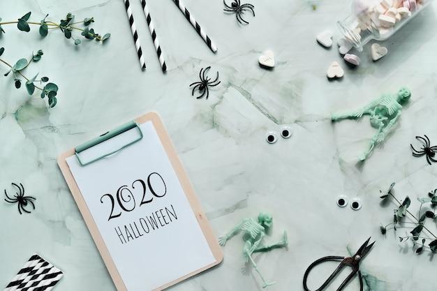 2020 texto de halloween en la libreta del portapapeles en piedra verde menta