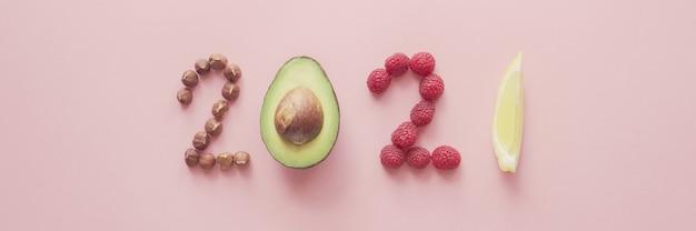 2021 elaborado con alimentos saludables en superficie rosa