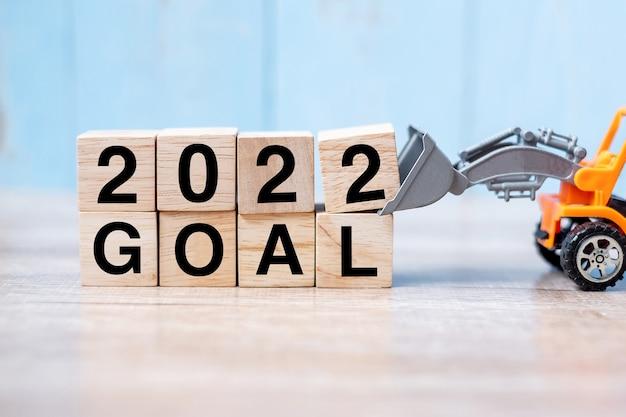 2022 bloques de cubos de meta con camión en miniatura o vehículo de construcción. nuevo comienzo, visión, resolución, objetivo, industrial, almacén y feliz año nuevo concepto