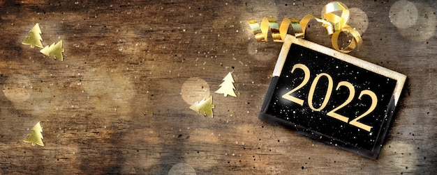 2022 escribiendo en una pequeña placa sobre fondo de madera rústica con confeti dorado y cinta