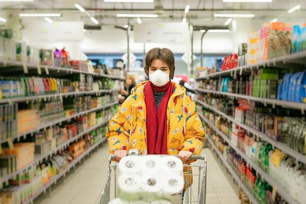 24.03.2020 rusia san petersburgo, una joven en una tienda con una máscara protectora selecciona productos