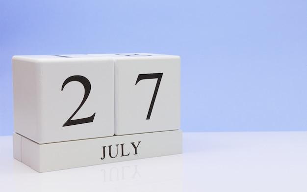 27 de julio. día 27 del mes, calendario diario en mesa blanca con reflejo, con fondo azul claro.