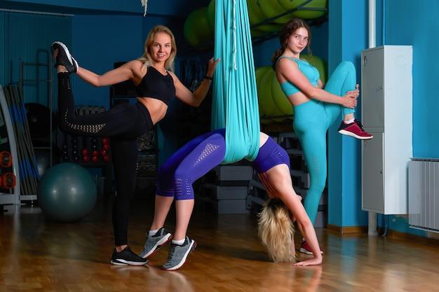 3 chicas practican deportes en un gimnasio