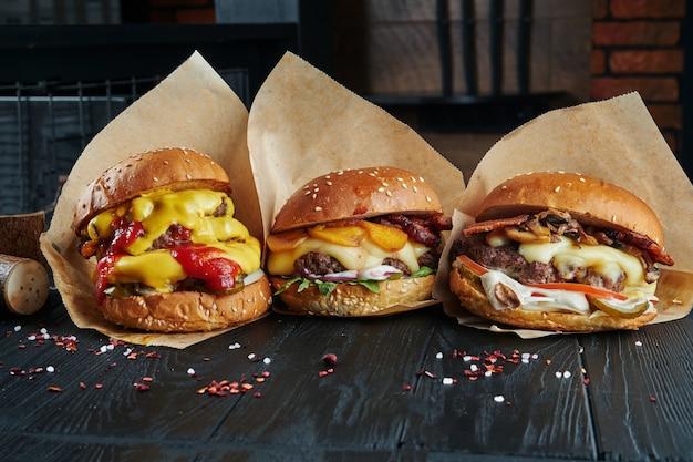3 deliciosas hamburguesas con diferentes rellenos en una mesa de madera negra. hamburguesa de piña con champiñones y queso cheddar derretido. establecer hamburguesa apetitosa