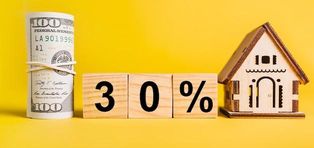 30 intereses con modelo de casa en miniatura y dinero sobre fondo amarillo. inversión, bienes raíces, hogar, vivienda, ganancias, concepto financiero