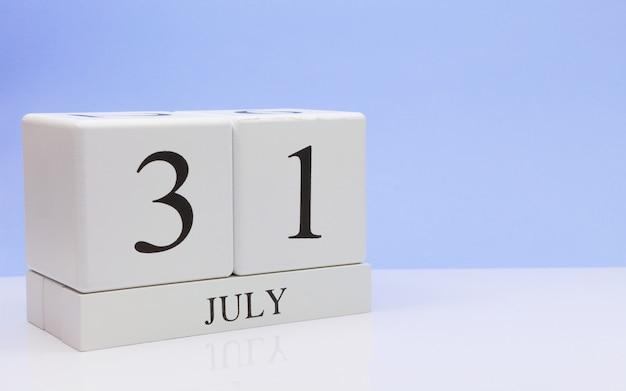 31 de julio. día 31 del mes, calendario diario en mesa blanca con reflejo, con fondo azul claro.