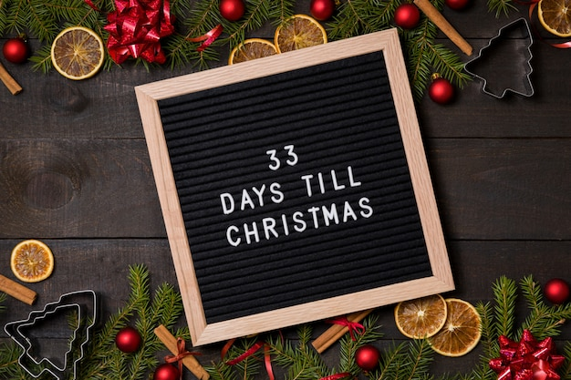 33 días hasta el tablero de la carta de cuenta regresiva de navidad sobre fondo de madera