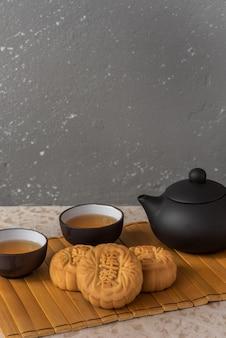 4 mini pasteles de luna de pasta de loto servidos con té chino