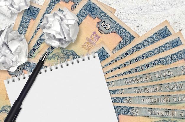 5 billetes de hryvnias ucranianas y bolas de papel arrugado con bloc de notas en blanco. malas ideas o menos concepto de inspiración. buscando ideas para inversión