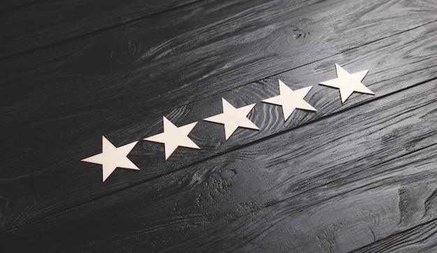 5 estrellas de madera sobre fondo negro. calificación de servicio