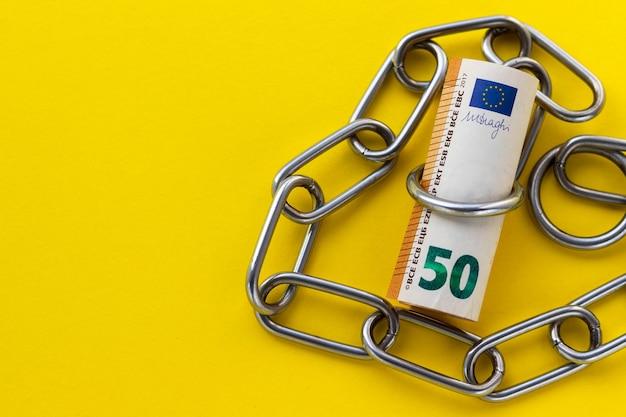50 euro bajo cadena metálica sobre fondo amarillo corrupción en ee.uu. finanzas