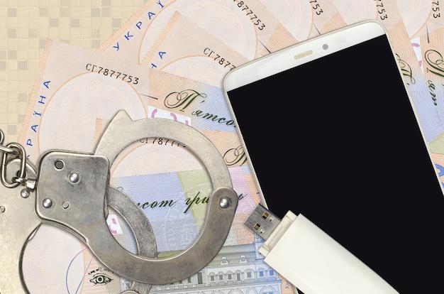 500 billetes de hryvnias ucranianas y smartphone con esposas de policía. concepto de ataques de phishing de piratas informáticos, estafa ilegal o distribución suave de software espía en línea