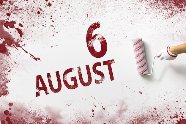 6 de agosto. día 6 del mes, fecha del calendario. la mano sostiene un rodillo con pintura roja y escribe una fecha del calendario sobre un fondo blanco. mes de verano, concepto de día del año.