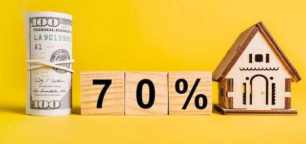 70 intereses con modelo de casa en miniatura y dinero sobre fondo amarillo.