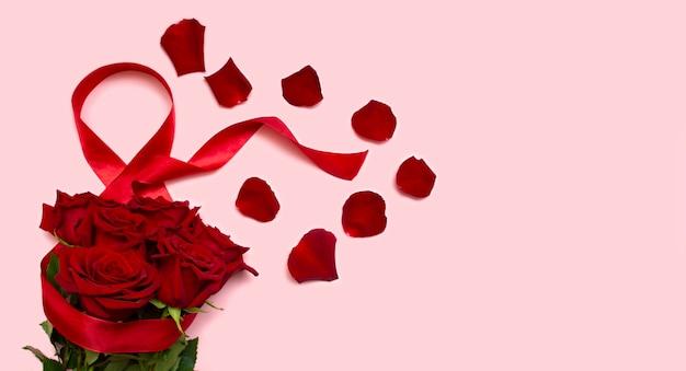 8 de marzo, el concepto de la fiesta del día internacional de la mujer, rosas rojas sobre un fondo rosa con una cinta roja y pétalos de rosa, un espacio en blanco para una postal, un lugar para el texto
