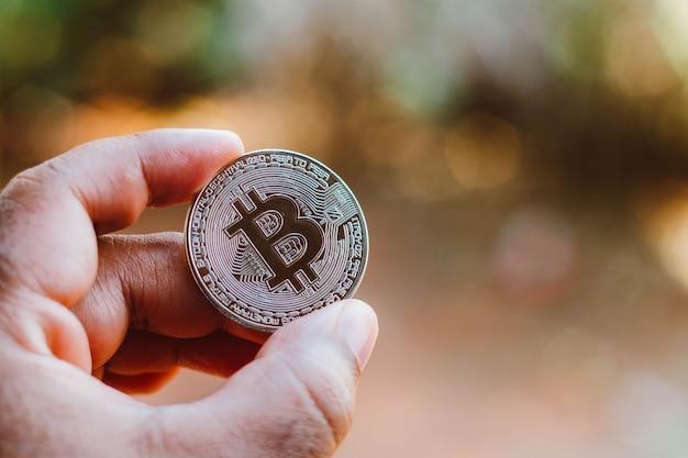 8 de septiembre de 2021, brasil. en esta ilustración fotográfica, un hombre muestra una moneda bitcoin de plata.