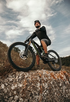 Desde abajo positivo hombre barbudo sentado en bicicleta y mirando hacia otro lado contra el cielo nublado durante el paseo por las tierras altas