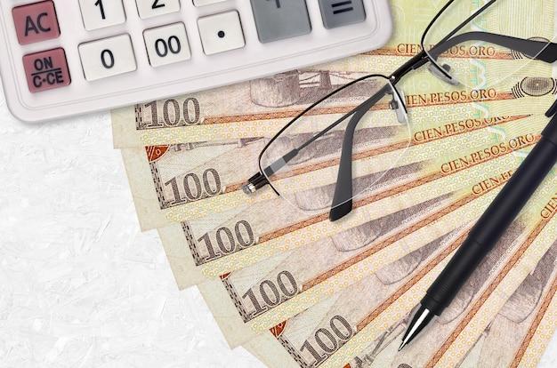 Abanico de billetes de 100 pesos dominicanos y calculadora con gafas y bolígrafo