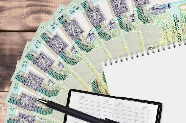 Abanico de billetes de 1000 rupias de sri lanka y bloc de notas con libreta de contactos y bolígrafo negro.
