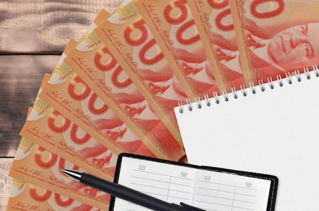 Abanico de billetes de 50 dólares canadienses y bloc de notas con libreta de contactos y bolígrafo negro