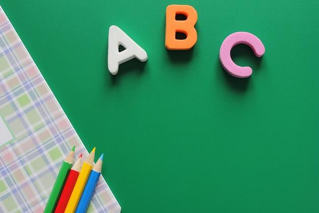 Abc-las primeras letras del alfabeto inglés. cuaderno escolar y lapices de colores