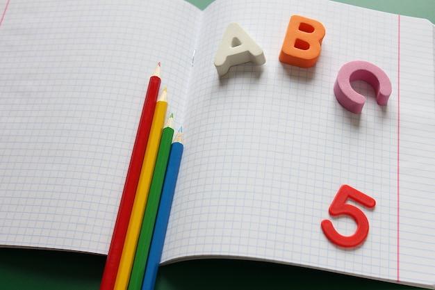 Abc: las primeras letras del alfabeto inglés y lápices de colores en el cuaderno de la escuela.